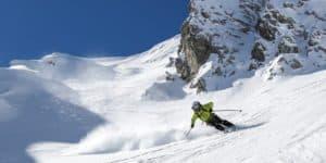 Mann in gelb-schwarzem Skianzug fährt mit Skiern eine Piste herab