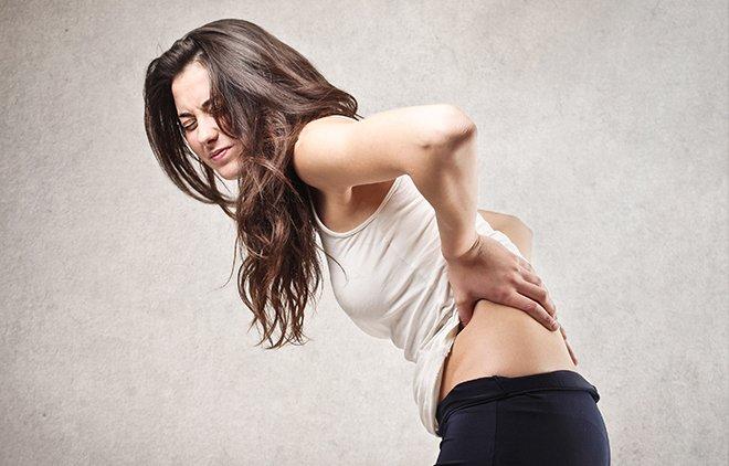 Braunhaarige Frau fasst sich mit schmerzverzerrtem Gesicht an den Rücken