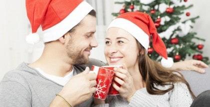 Ehepaar sitzt mit Weihnachtsmützen und Tassen auf dem Sofa vor einem Weihnachtsbaum