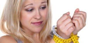 Blonde Frau mit Maßband als Fessel um die Handgelenke gewickelt