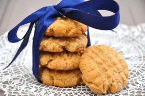 4 aufeinandergestapelte Erdnussbuttercookies, zusammengehalten durch eine große blaue, seidene Schleife