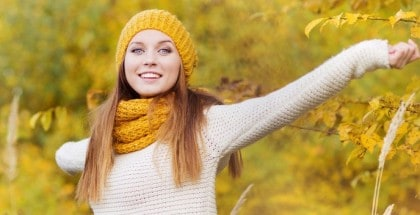 Glückliche Frau mit gelbem Schal und gelber Mütze