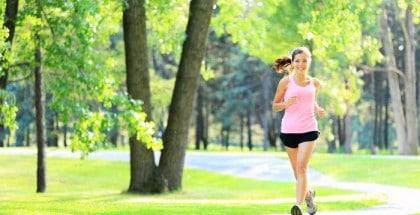 Joggerin läuft durch einen grünen Park