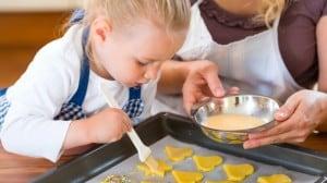 Kind bestreicht gelbe Plätzchen in Herzform