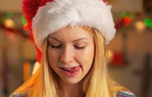 Frau mit Weihnachtsmuetze und gierigem Blick