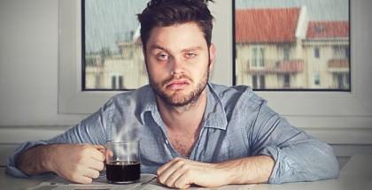 Mann mit Hang-Over vor einer halb gefüllten Kaffeetassee