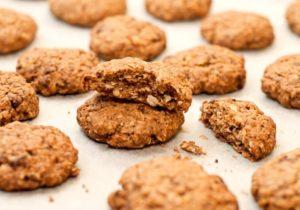 Nuss-Haferflocken-Schokocookies auf einem Backblech mit weißem Backpapier