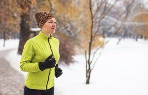 Frau mit Mütze und Handschuhen joggt im Winter.