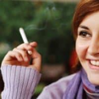 Eine lächelnde Raucherin mit violettem Pullover