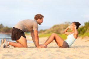 Mann und frau am Sandstrand machen Sit Ups