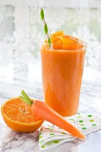 1 Glas A-C-E-Smoothie mit Strohhalm. Davor eine halbe Orange und eine Karotte
