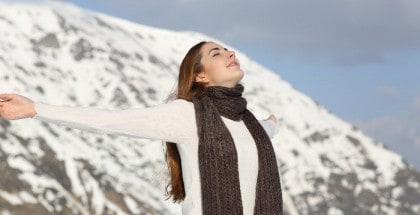 Frau in weißem Pullover und mit braunem Schal breitet mit geschlossenen Augen die Arme aus und atmet tief ein