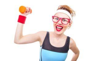 Frau im lustigen Sportdress hebt eine orange Hantel in die Höhe