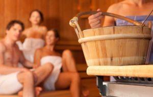 In einer Sauna: Drei Frauen und ein Mann, die mit weißen Handtüchern bekleidet sind