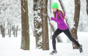 Frau im wintertauglichen Fitness-Outfit joggt durch den Wald