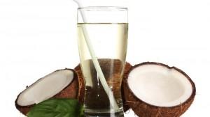 Glas Kokoswasser und zwei Kokosnusshälften