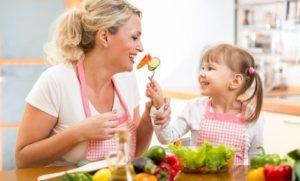 Mama und Kind beim Essen von gesundem Gemüse