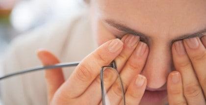 Im Büro arbeitende Frau, die sich vor Müdigkeit die Augen reibt