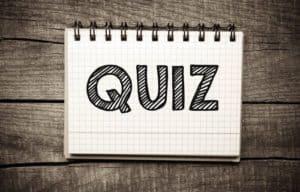 Ein Block, der auf einem Tisch liegt und das Wort Quiz drauf stehen hat.