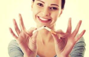 Lächelnde Frau, die eine Zigarette zerbricht