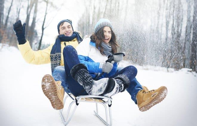 Mann und Frau rodeln auf einem Schlitten den Berg herab