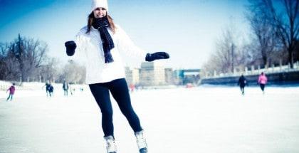 Frau in weißer Jacke und schwarzer Hose läuft Schlittschuhe auf zugefrorenem See