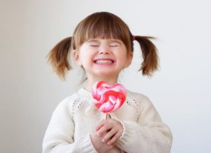 Strahlend grinsendes Mädchen mit einem Lutscher in der Hand