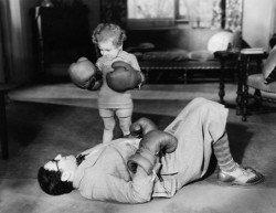 Kind schlägt Mann ko mit Boxhandschuhen.