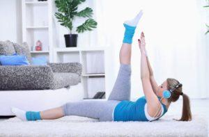 Frau im Wohnzimmer in Sportkleidung dehnt sich