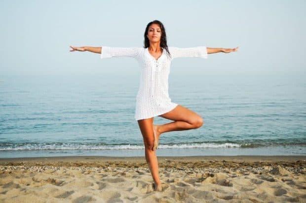 Frau steht am Strand in Waage Yoga Position weißes Kleid