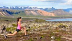 Frau macht Lunge im Freien, im Hintergrund Berge