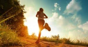 Frau joggt in den Sonnenuntergang.