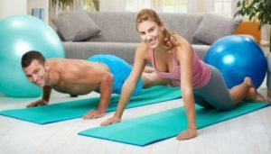 MAnn Frau auf Sportmatte im Wohnzimmer machen Sit Ups