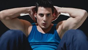 Mann mit blauem Shirt macht Sit Ups schwarzer Hintergrund