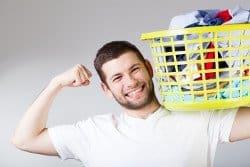 Mann mit Wäschekorb auf der Schulter freut sich.