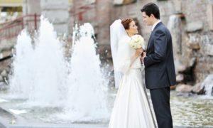 Frisch vermähltes Paar vor Mauer