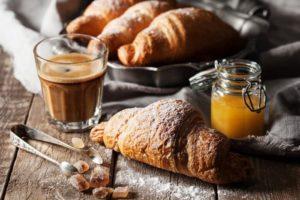 Croissant in Mehl auf Holztisch mit Glas Kaffee.