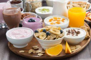 großes Tablet mit Müsli, Säften und anderen Frühstücksutensilien