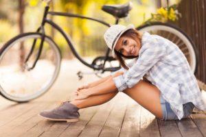 Frau sitzt auf Holzbrücke, im Hintergrund steht ein Fahrrad