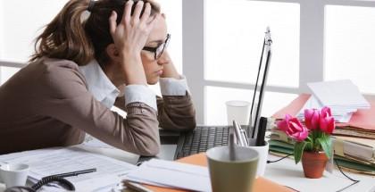 Frau vorm Laptop ist gestresst und fasst sich an den Kopf