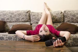 Frau liegt falsch herum mit Fernbedienung auf dem Sofa