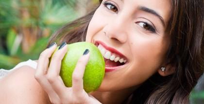Frau beisst in grünen Apfel