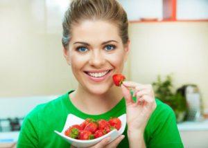 Frau isst eine Schüssel Erdbeeren