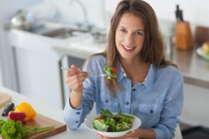 Frau in blauem Jeanshemd isst Salat