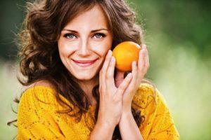 Frau mit gelbem Pullover hält Orange