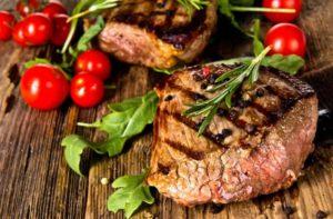 Steak mit Tomaten liegt auf Tisch
