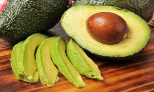 Avocados als ganze Frucht, halbiert und in Streifen geschnitten