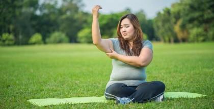 Asiatische Frau, die mit trauriger Miene ihr überschüssiges Winkfett am rechten Oberarm begutachtet