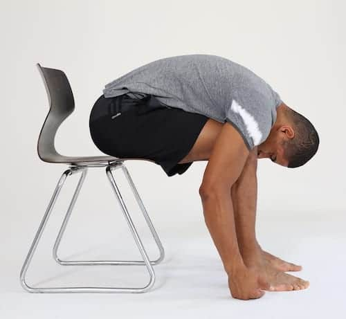 Mann sitzt auf Stuhl und beugt sich nach vorne in die Vorbeuge