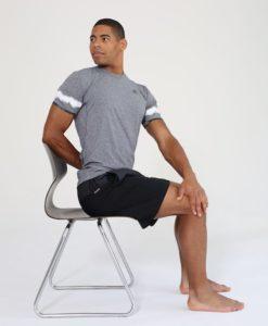 Mann sitzt auf Stuhl und dreht sich mit geradem Rücken in den Twist